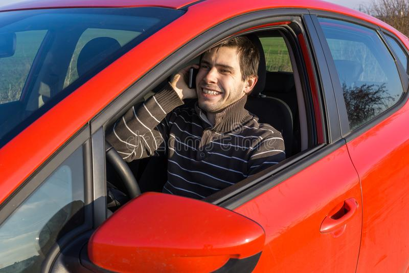 El hombre está conduciendo un coche, los controles llaman por teléfono y llamando con alguien imágenes de archivo libres de regalías