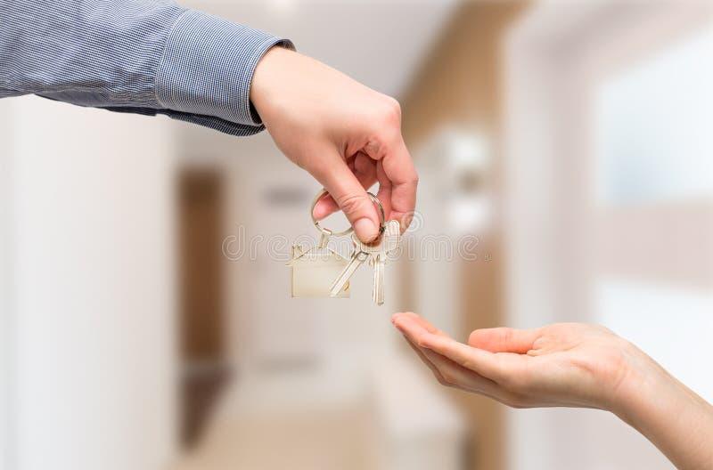 El hombre está dando un clave de la casa a una mujer Conceptos de las propiedades inmobiliarias imagenes de archivo