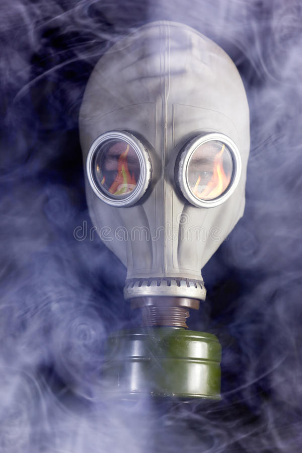 El hombre está en careta antigás con humo alrededor imagenes de archivo