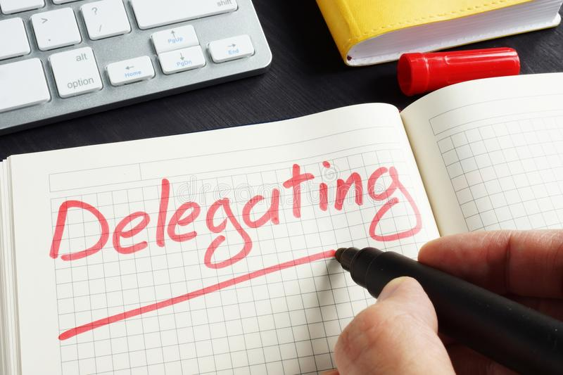 El hombre está escribiendo la delegación en la libreta Concepto del delegado imagen de archivo libre de regalías