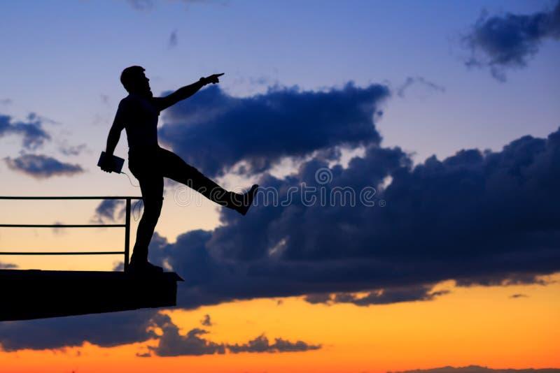El hombre está escuchando la música en el tejado Nubes y puesta del sol fotografía de archivo