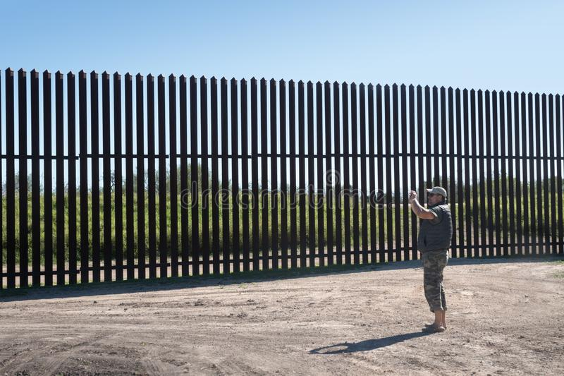 """El hombre está fotografiando la barrera de nuevo Mexico†""""Estados Unidos del hierro en el campo Tejas fotografía de archivo"""