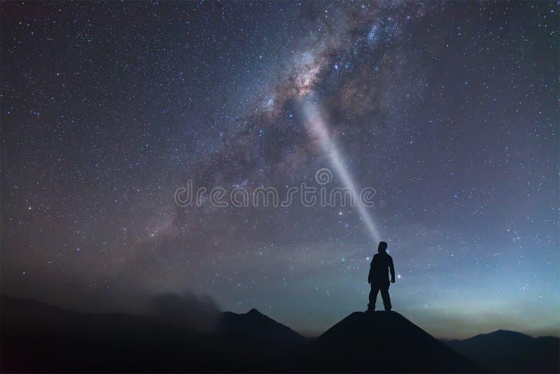 El hombre está haciendo frente en la colina y la luz a la vía láctea fotos de archivo libres de regalías