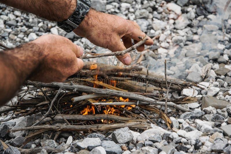 El hombre está haciendo el fuego en naturaleza fotos de archivo libres de regalías