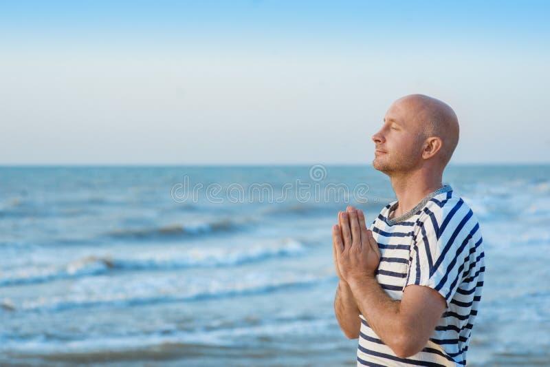 El hombre está haciendo una pausa el mar y está rogando a dios imagen de archivo