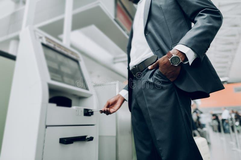 El hombre está insertando la tarjeta de banco en el aeropuerto foto de archivo libre de regalías