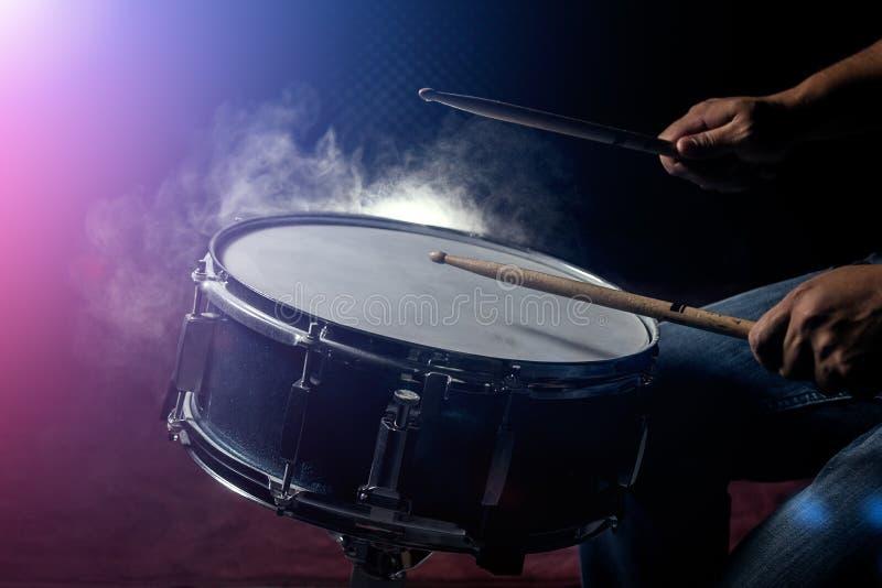 El hombre está jugando el tambor en fondo de la luz corta imágenes de archivo libres de regalías