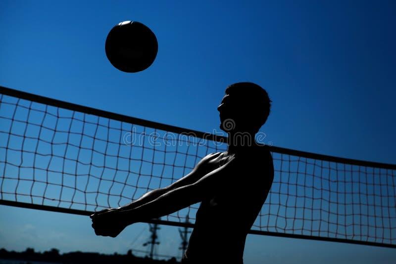 El hombre está jugando a voleibol imagen de archivo