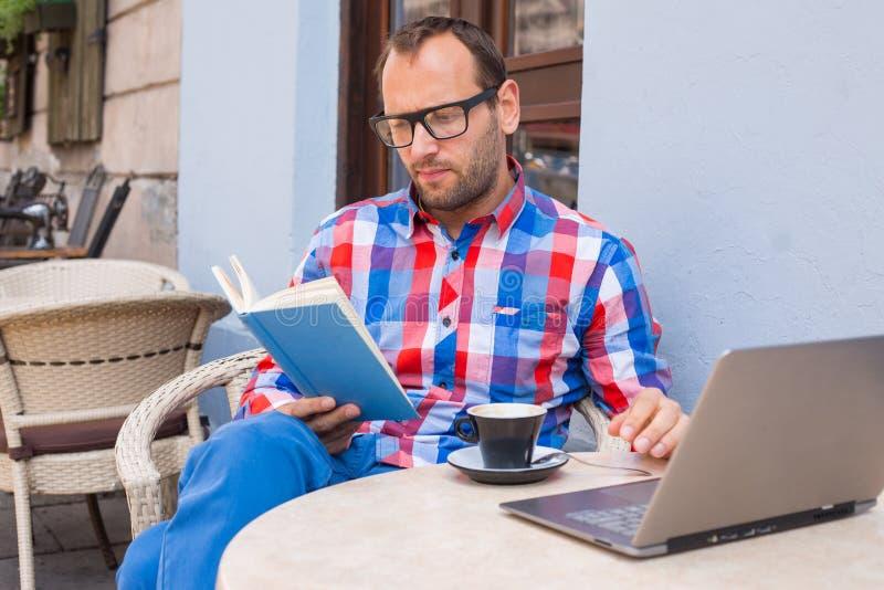 El hombre está leyendo un libro en café. Él está bebiendo el café. imagen de archivo