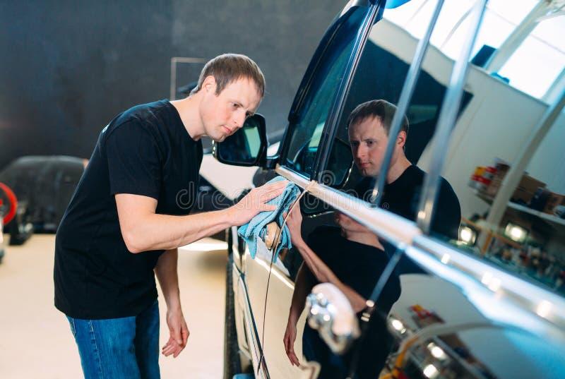 El hombre está limpiando con un cuerpo del paño de un coche brillante foto de archivo