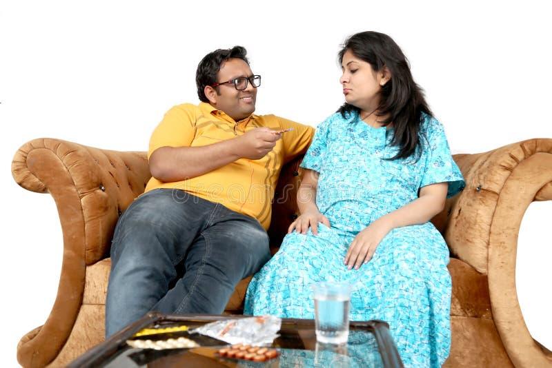 El hombre está llevando a cabo la medicina a disposición y embarazada irrite a la esposa está viendo la medicina imagen de archivo