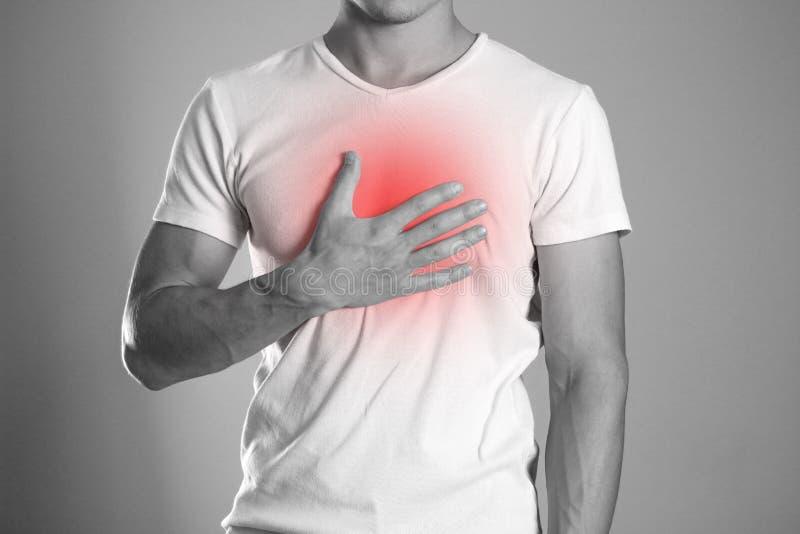 El hombre está llevando a cabo su dolor de pecho del pecho heartburn El hogar foto de archivo libre de regalías