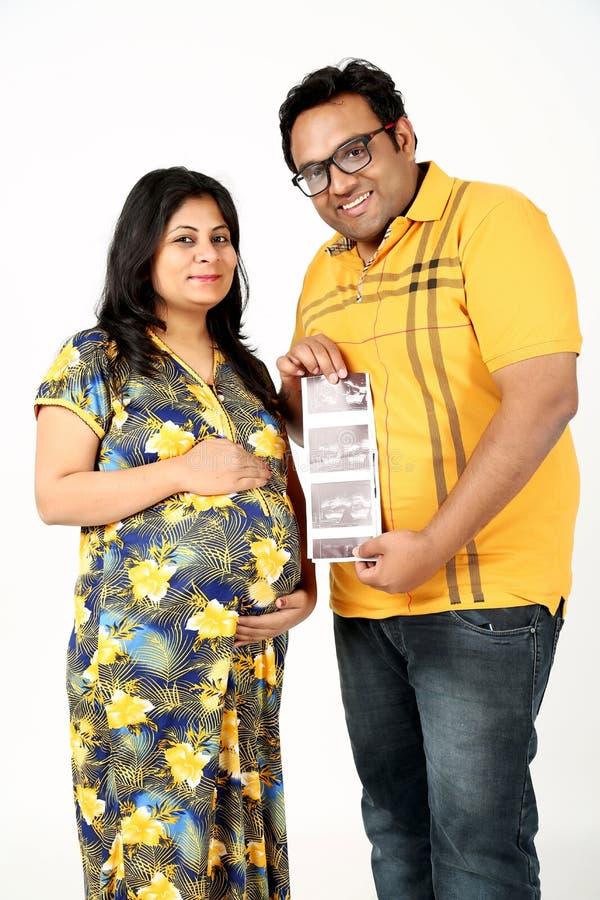 El hombre está llevando a cabo ultrasonido a disposición con la esposa embarazada imagen de archivo libre de regalías
