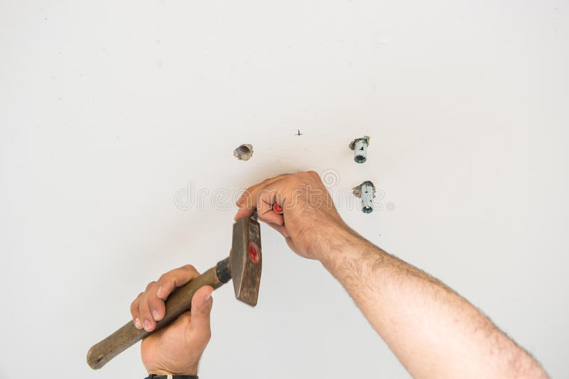 El hombre está martillando los pasadores del metal en techo concreto fotos de archivo
