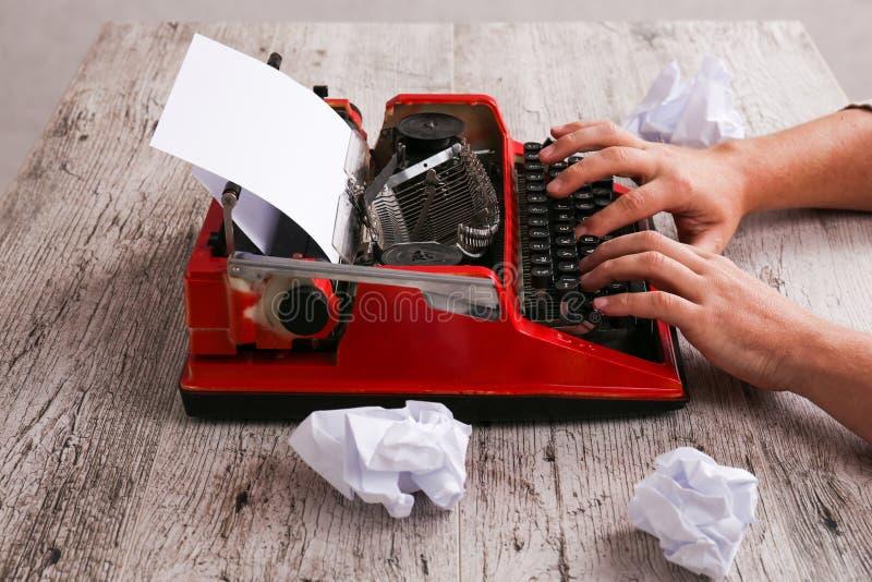 El hombre está mecanografiando y al lado de las hojas de papel arrugadas fotografía de archivo libre de regalías