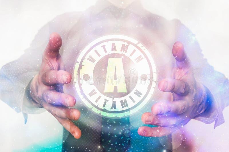 El hombre está mostrando símbolo de la vitamina A entre sus manos fotografía de archivo libre de regalías