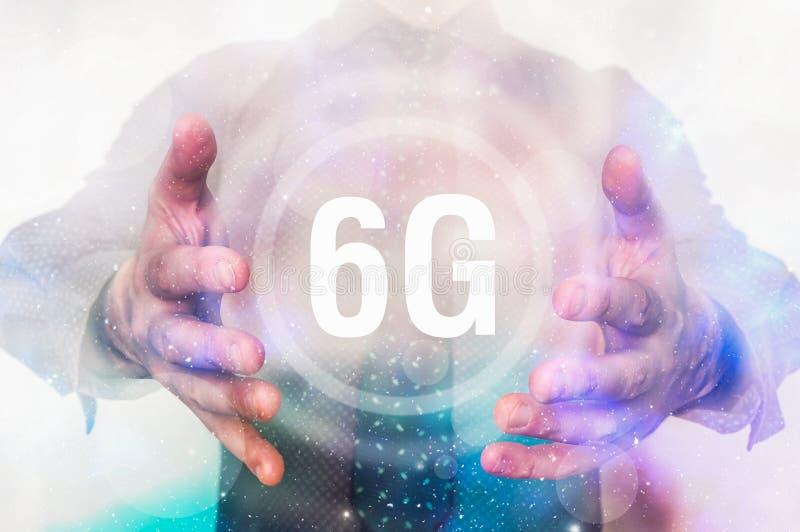 El hombre está mostrando símbolo del interfaz 6G entre sus manos fotos de archivo