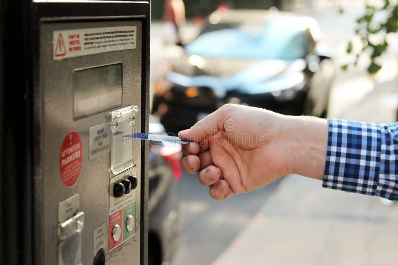 El hombre está pagando su estacionamiento usando tarjeta de crédito en el terminal de la estación de la paga del estacionamiento fotos de archivo libres de regalías