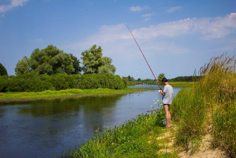 El hombre está pescando en el banco del río con una caña de pescar en verano fotos de archivo libres de regalías