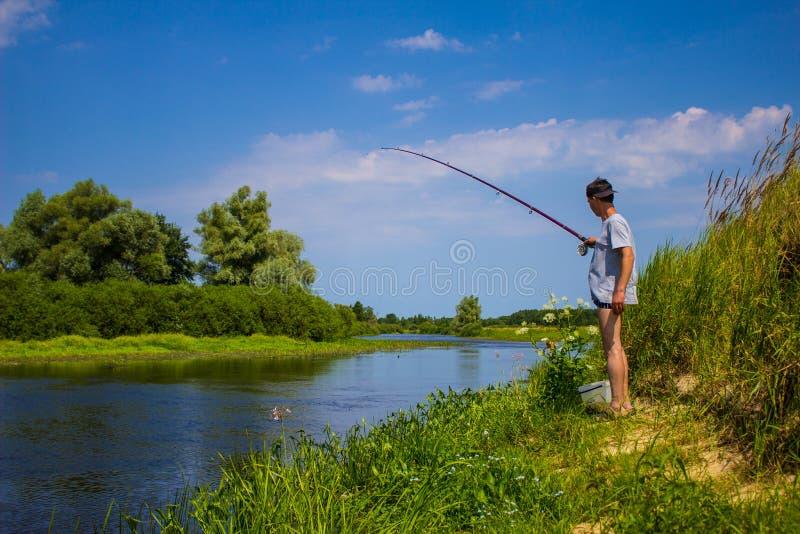 El hombre está pescando en el banco del río con una caña de pescar en verano fotografía de archivo