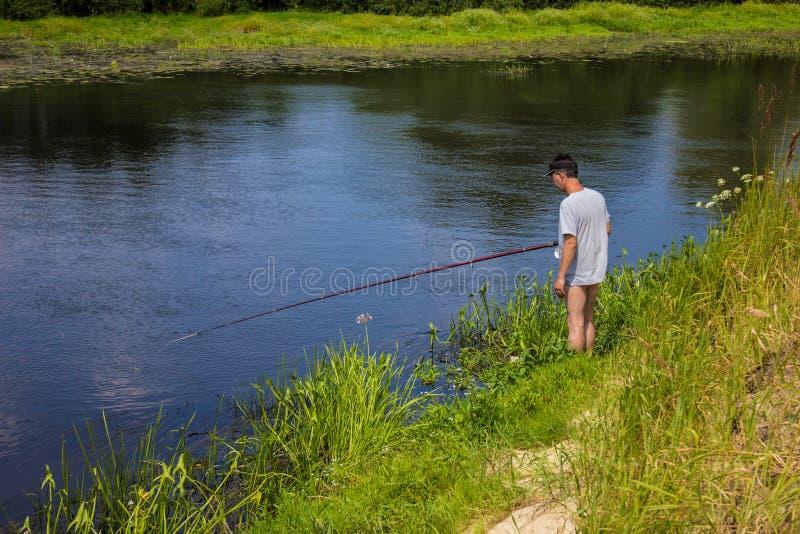El hombre está pescando en el banco del río con una caña de pescar en verano imagen de archivo