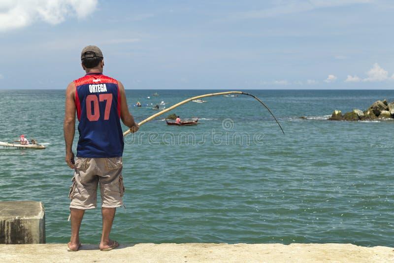 El hombre está pescando en el mar del embarcadero fotografía de archivo libre de regalías