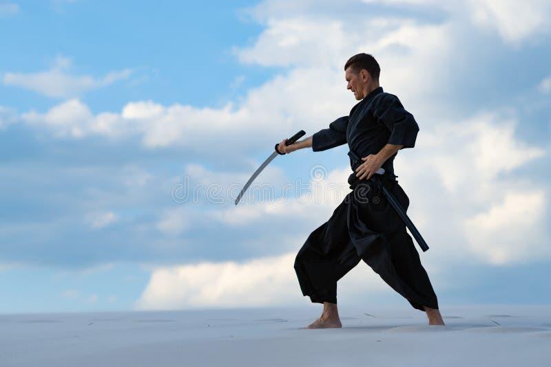 El hombre está practicando el arte marcial japonés - iaido fotografía de archivo