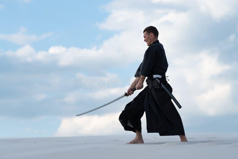 El hombre está practicando el arte marcial japonés - iaido fotos de archivo libres de regalías