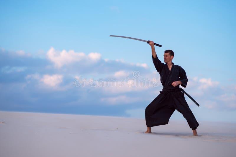 El hombre está practicando con una espada japonesa - un katana imagen de archivo