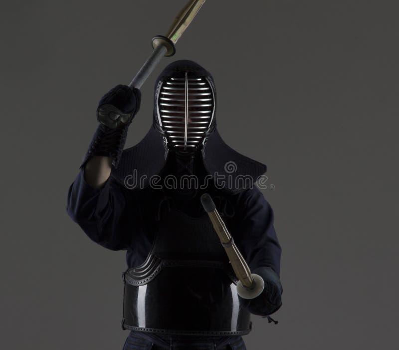 El hombre está practicando kendo en armadura tradicional Él que balancea con dos espadas de bambú imágenes de archivo libres de regalías