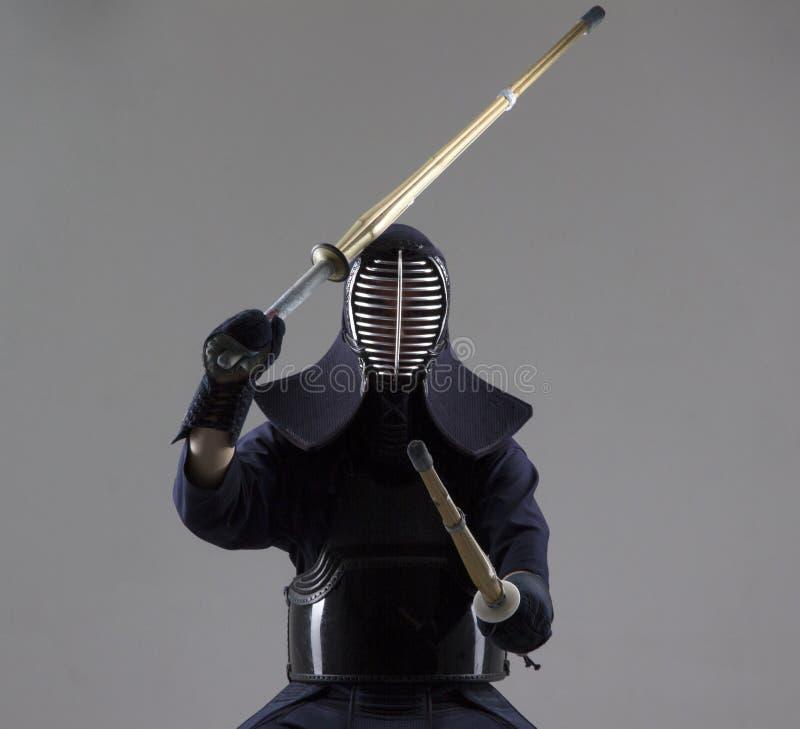 El hombre está practicando kendo en armadura tradicional Él que balancea con dos espadas de bambú foto de archivo libre de regalías
