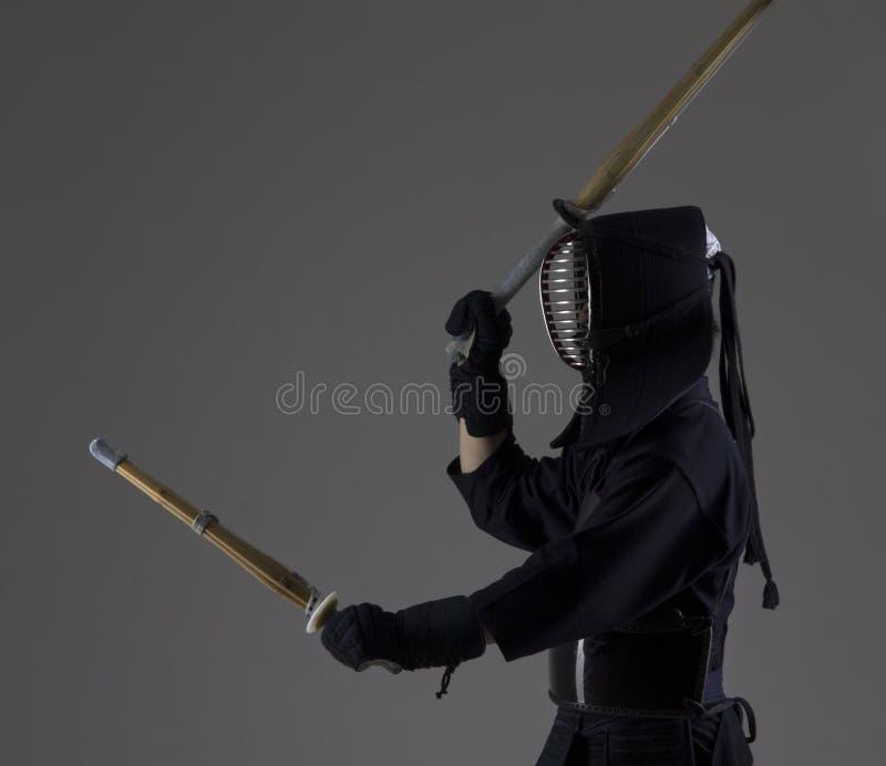 El hombre está practicando kendo en armadura tradicional Él que balancea con dos espadas de bambú imagen de archivo libre de regalías