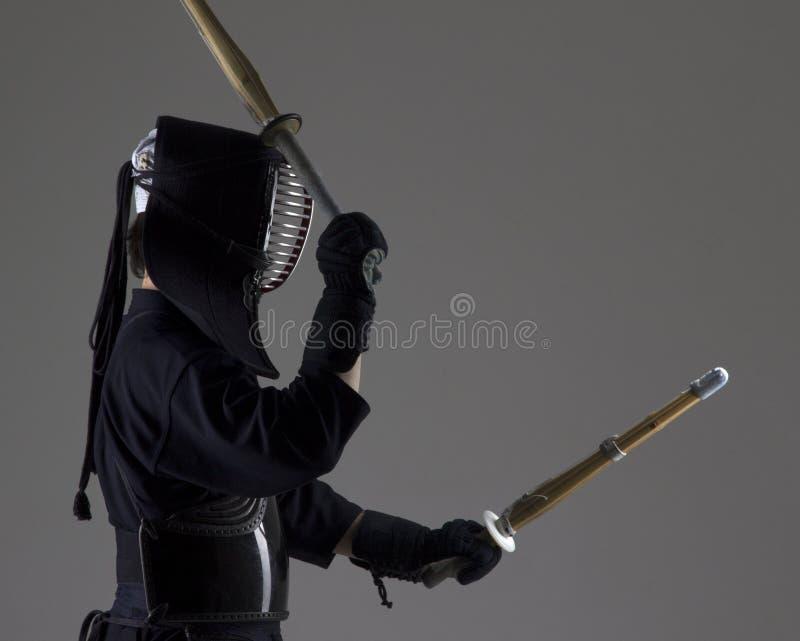 El hombre está practicando kendo en armadura tradicional Él que balancea con dos espadas de bambú imagen de archivo