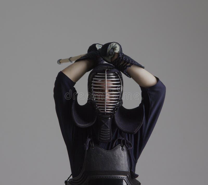 El hombre está practicando kendo en armadura tradicional Él que balancea con la espada de bambú foto de archivo libre de regalías