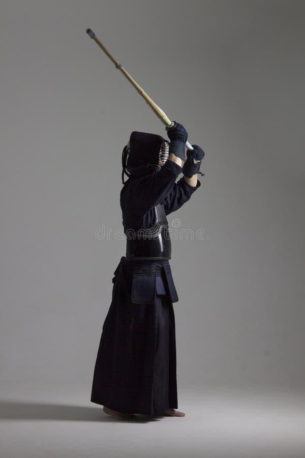 El hombre está practicando kendo en armadura tradicional Él que balancea con la espada de bambú fotografía de archivo