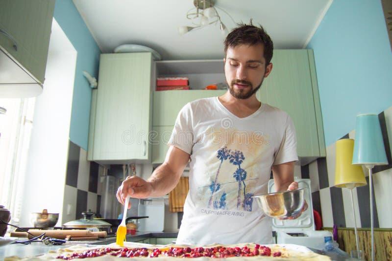 El hombre está preparando un milhojas de la cereza fotografía de archivo libre de regalías