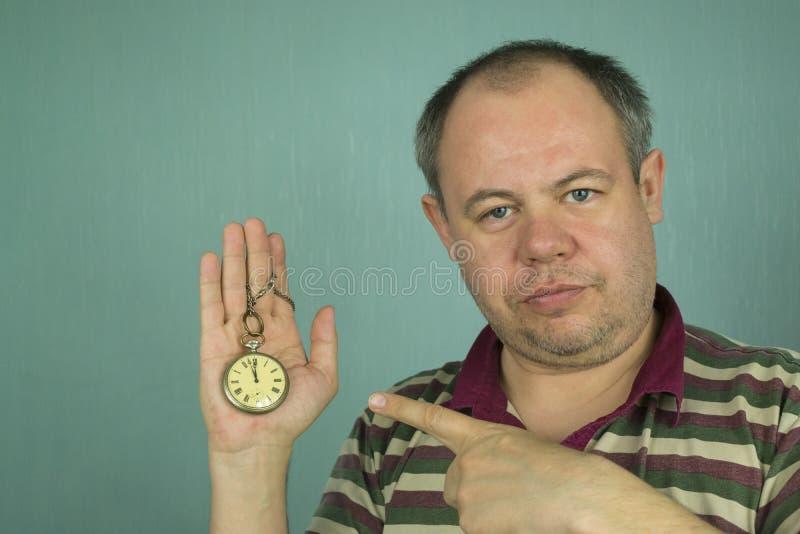 El hombre está señalando en el reloj imagenes de archivo