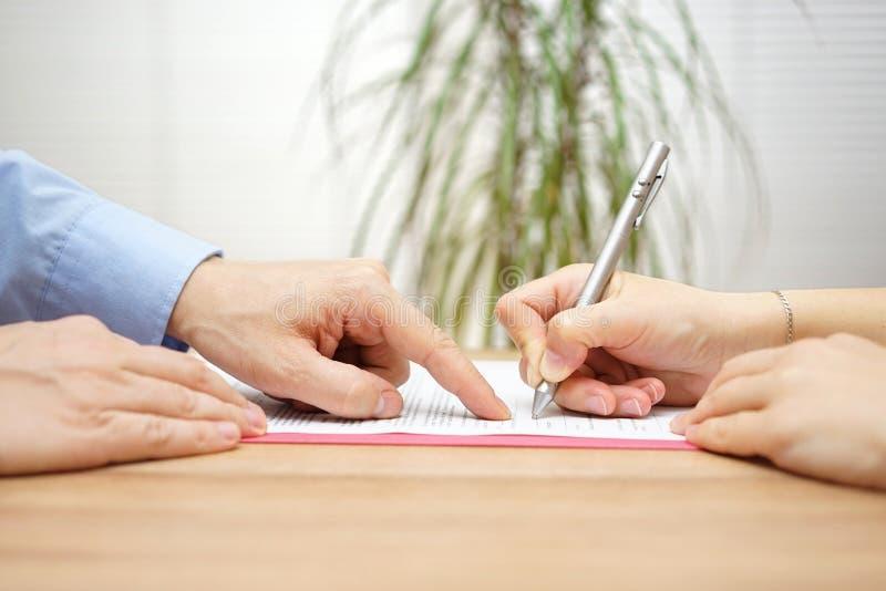 El hombre está señalando un lugar en donde ella debe firmar el acuerdo imagen de archivo libre de regalías