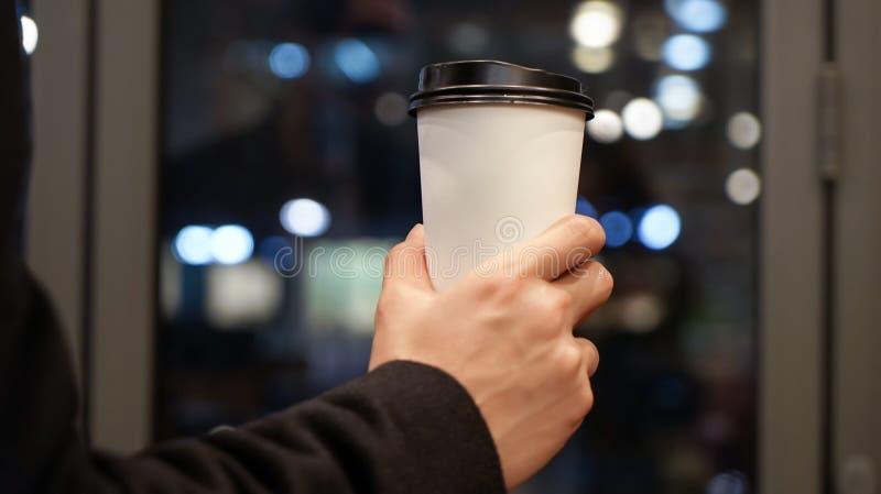 El hombre está sosteniendo la taza de café de papel con un casquillo plástico marrón imagenes de archivo