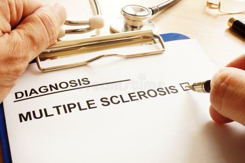 El hombre está sosteniendo el tablero con esclerosis múltiple foto de archivo libre de regalías