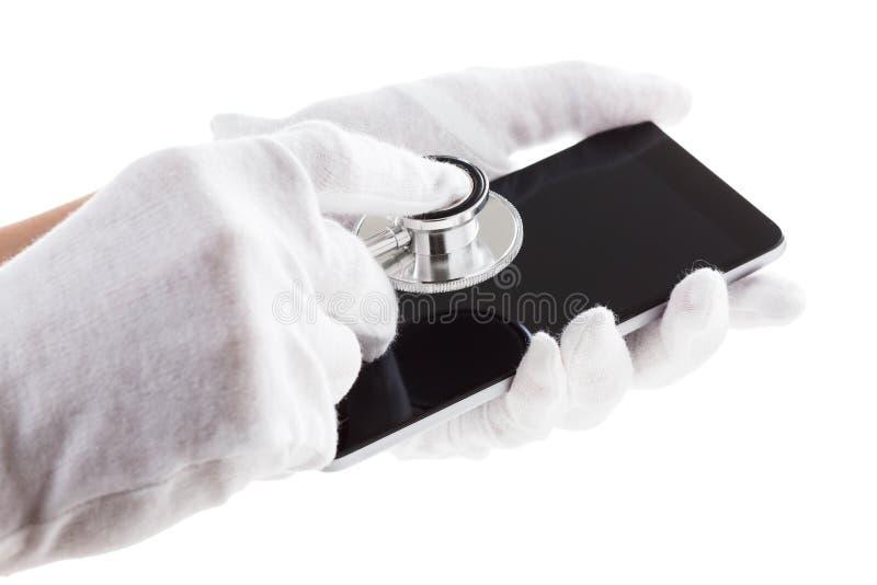 El hombre está sosteniendo el teléfono móvil elegante con las herramientas del phonendoscope en la pantalla imagen de archivo