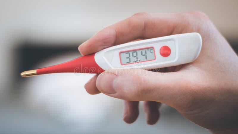 El hombre está sosteniendo un termómetro de la fiebre en su mano foto de archivo libre de regalías
