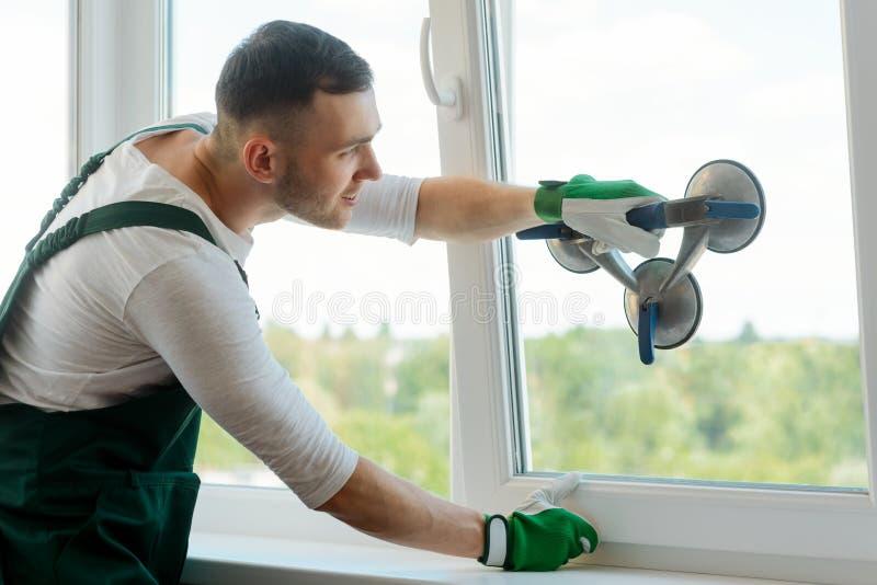 El hombre está substituyendo el vidrio en ventana foto de archivo libre de regalías