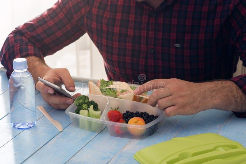 El hombre está teniendo comida sana del almuerzo que se sienta en la tabla de madera imagenes de archivo