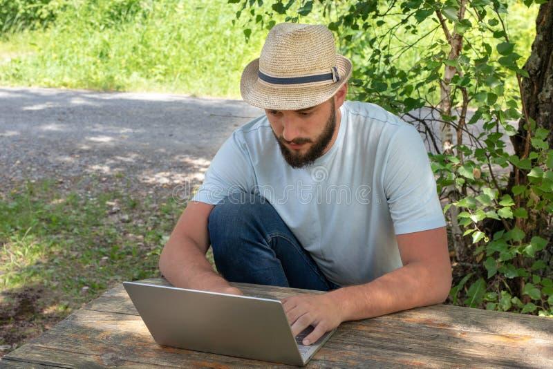 El hombre está trabajando difícilmente en un ordenador en naturaleza El concepto de trabajo remoto, oficina, independiente foto de archivo