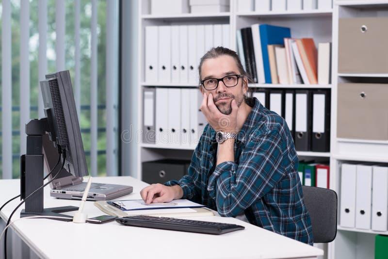 El hombre está trabajando en su oficina foto de archivo libre de regalías