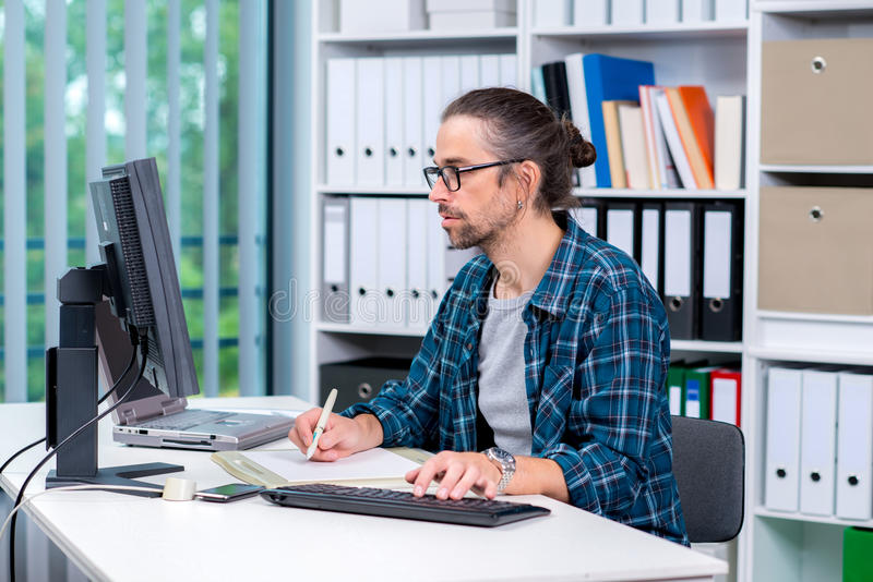 El hombre está trabajando en su oficina imagen de archivo libre de regalías
