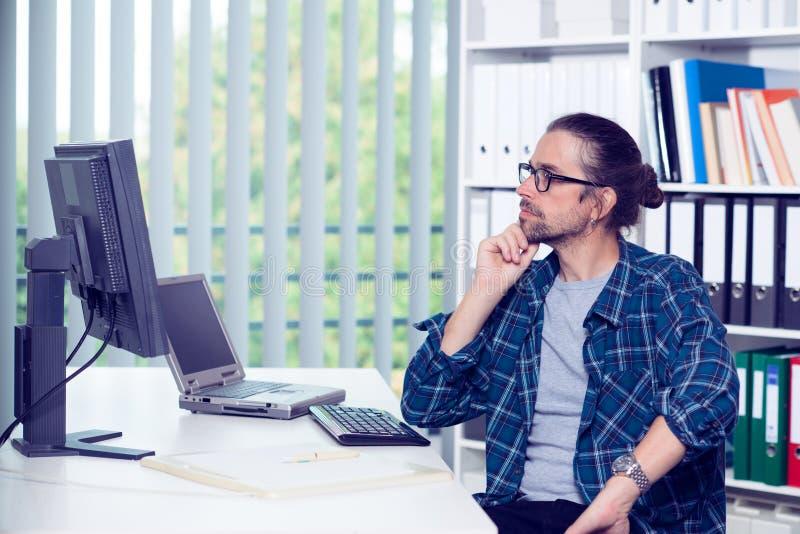 El hombre está trabajando en su oficina y está mirando para supervisar imagen de archivo libre de regalías