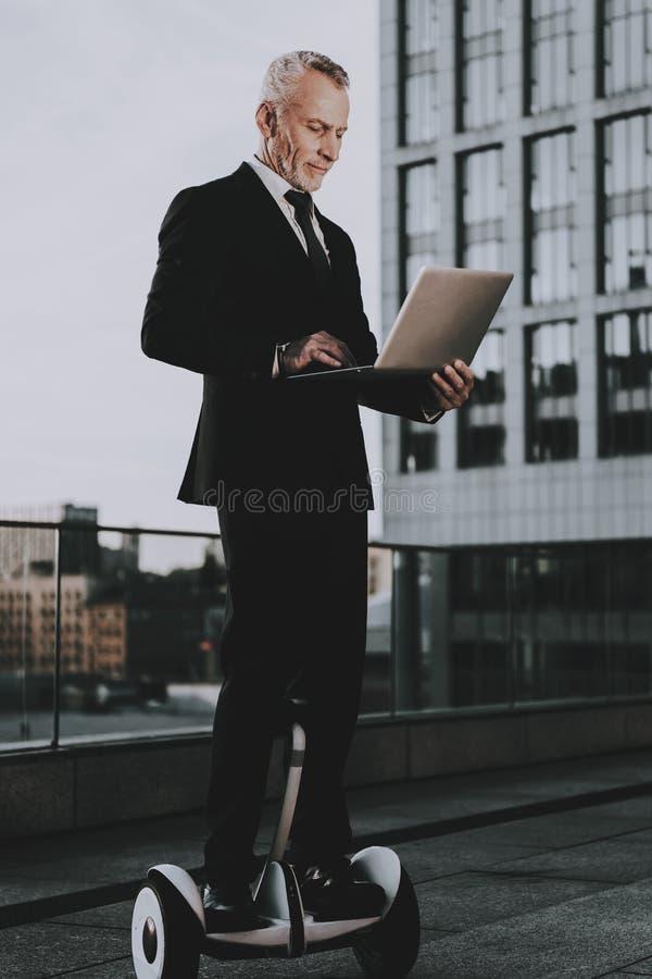 El hombre está utilizando un ordenador portátil en Gyroboard fotos de archivo