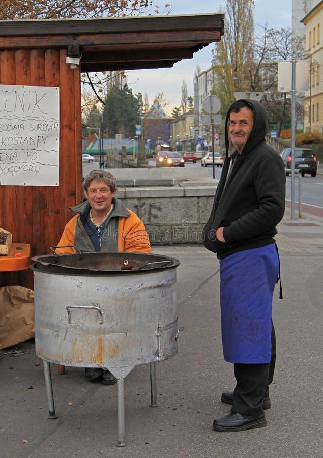 El hombre está vendiendo las castañas asadas en el quiosco en Maribor, Eslovenia imagen de archivo libre de regalías